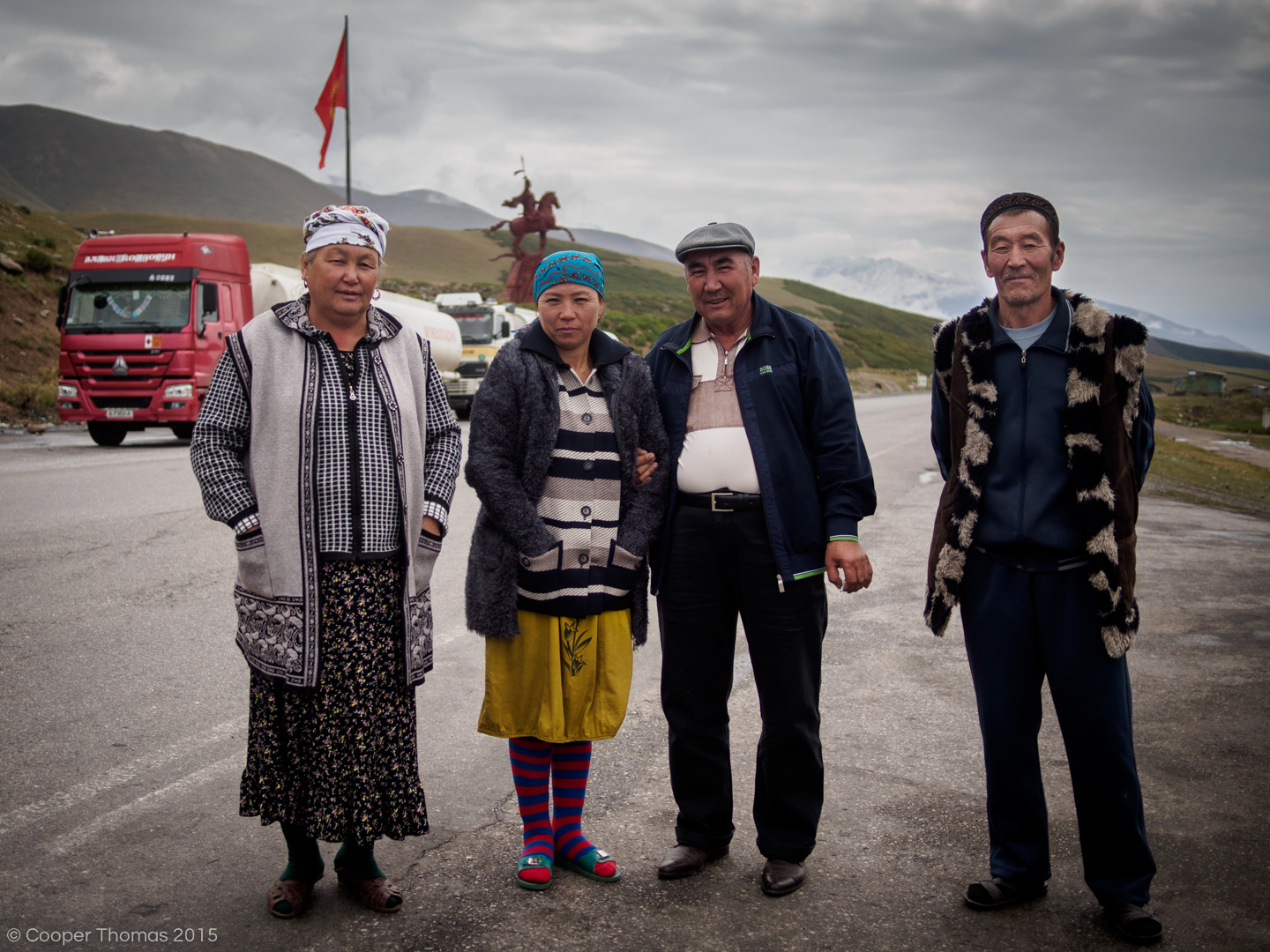 Locals pose near a Manas Statue, which marks the M41's junction with the main road to Talas Oblast