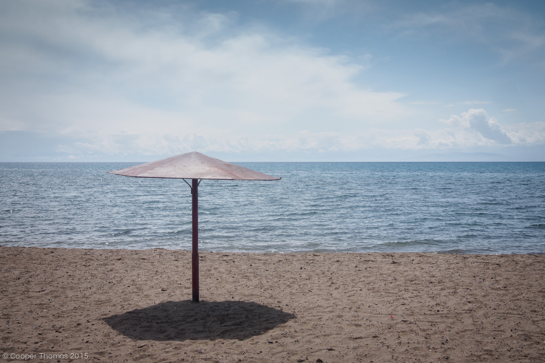 Unoccupied metal umbrella on the beach